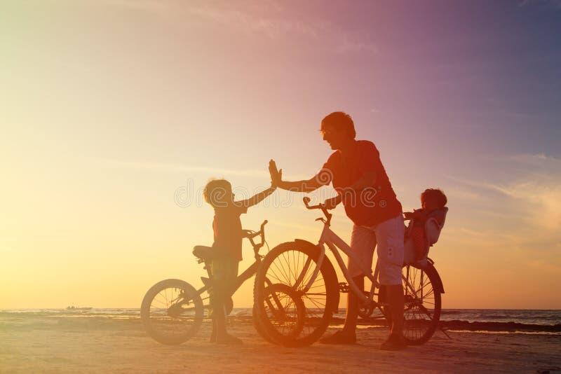Het silhouet van de fietserfamilie, vader met twee jonge geitjes  royalty-vrije stock afbeeldingen