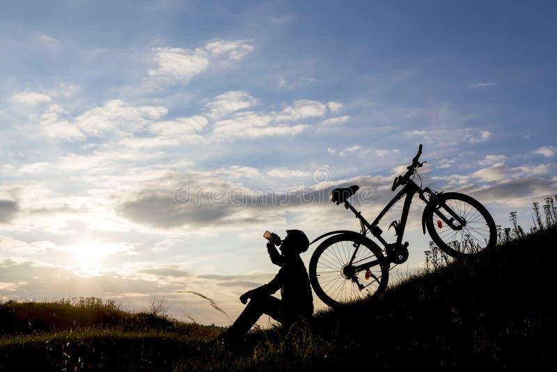 Het silhouet van de fietsermens en bergfiets stock afbeeldingen