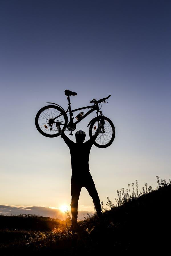 Het silhouet van de fietsermens en bergfiets royalty-vrije stock afbeeldingen