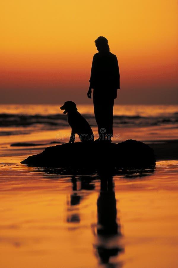 Het silhouet van de mens en van de hond royalty-vrije stock afbeeldingen