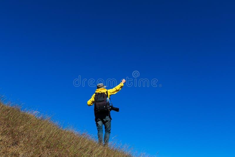 Het silhouet van de mens steunt handen op de piek van berg, succesconcept stock foto's