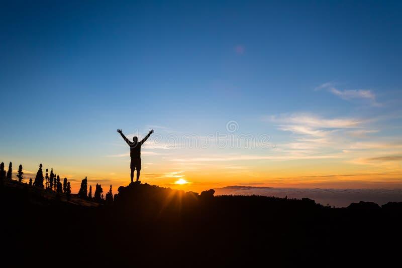 Het silhouet van de mensenwandelaar met uitgestrekte wapens geniet van bergen stock afbeeldingen