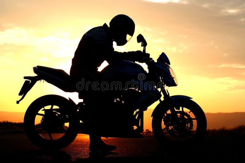 Het silhouet van de motorrijder bij de zonsondergang stock afbeeldingen