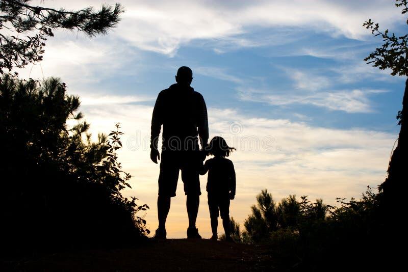 Het silhouet van de vader en van de dochter stock foto