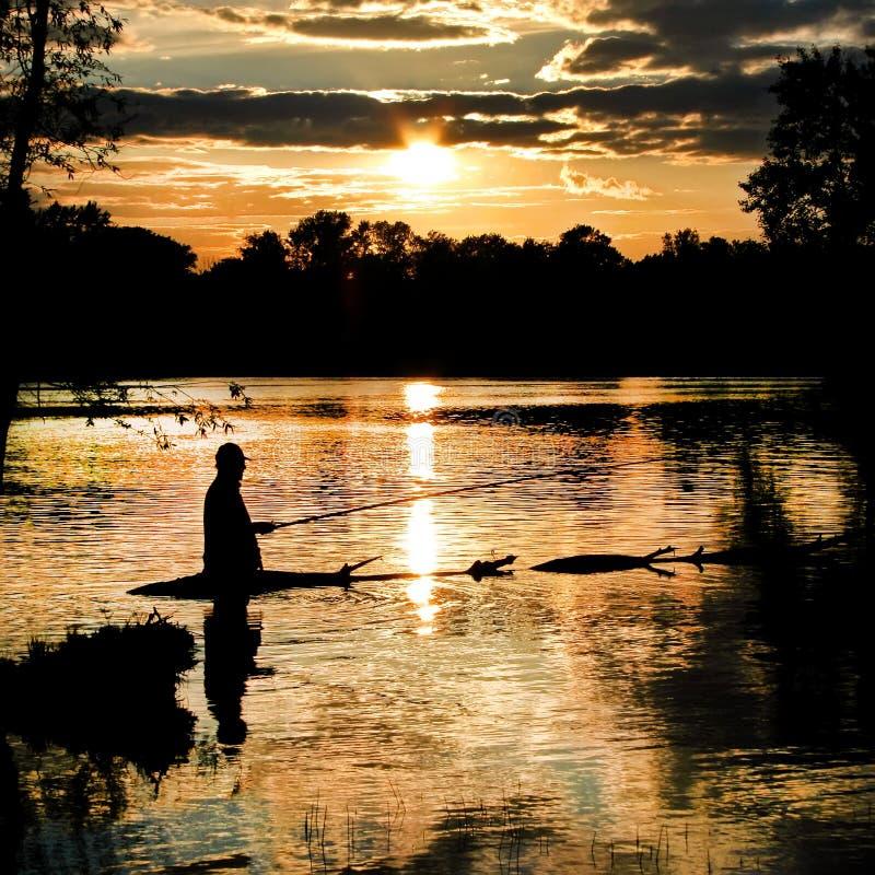 Het silhouet van de visser bij de visserij op zonsondergang De Zwart-witte foto van Peking, China stock foto's