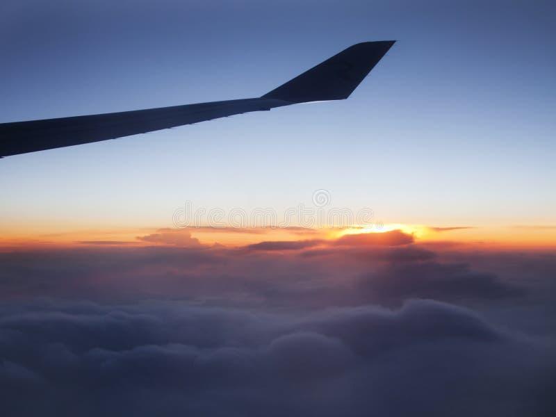 Het silhouet van de vliegtuigvleugel bij zonsonderganghemel royalty-vrije stock fotografie