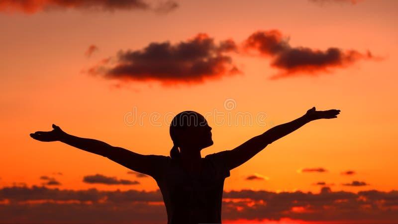 Het silhouet van de vrouw op zonsonderganglicht stock fotografie