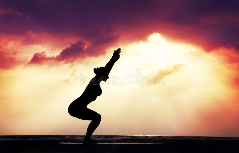 Het silhouet van de yoga op het strand stock foto