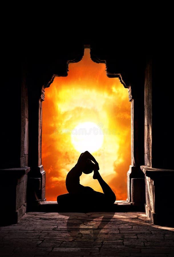 Het silhouet van de yoga in tempel stock foto's