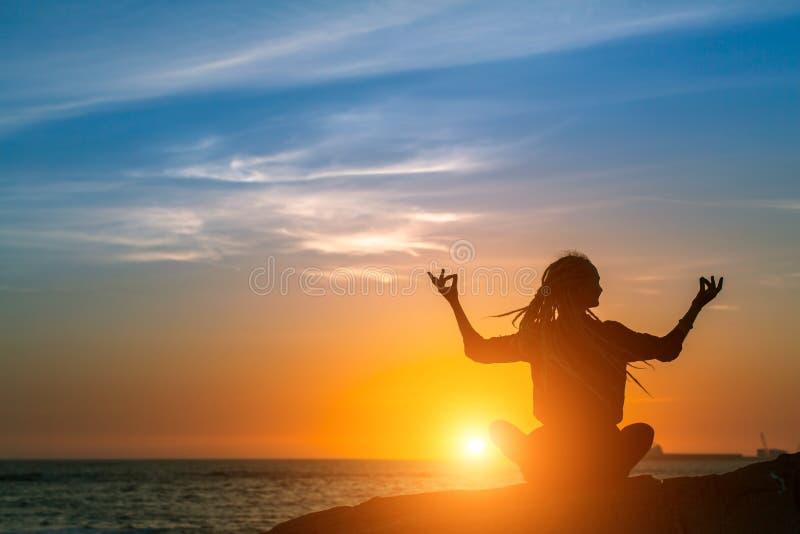 Het silhouet van de yogavrouw Meditatie op de oceaan tijdens verbazende zonsondergang stock afbeelding