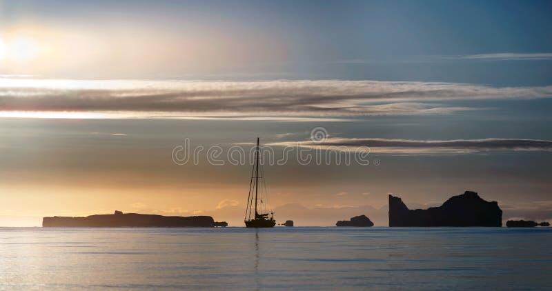 Het silhouet van de zeilboot en de ijsbergen bij zonsondergang royalty-vrije stock foto