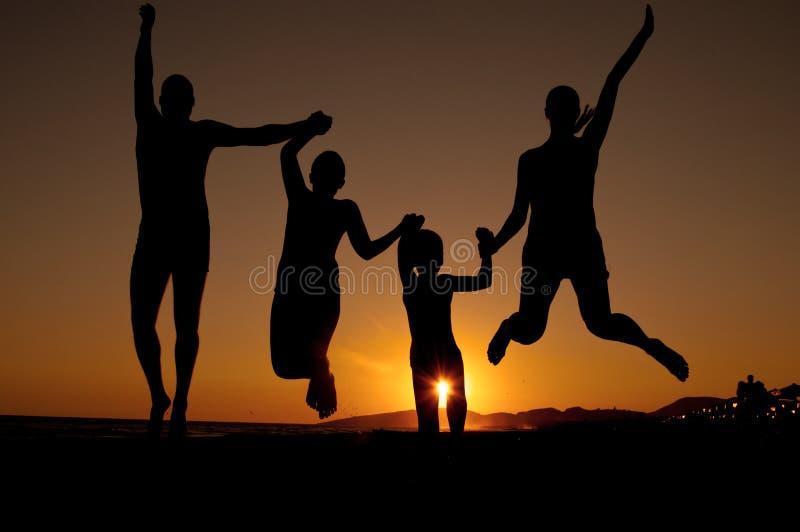 Het silhouet van de zonsondergang van familie stock afbeelding
