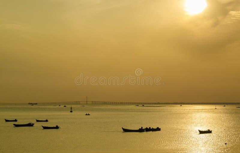 Het silhouet van een boot in de het plaatsen zon stock fotografie