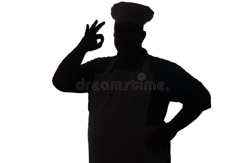 Het silhouet van een gelukkige chef-kok op een wit isoleerde achtergrond, toont de mannelijke hand o.k., het concept van de voeds stock fotografie