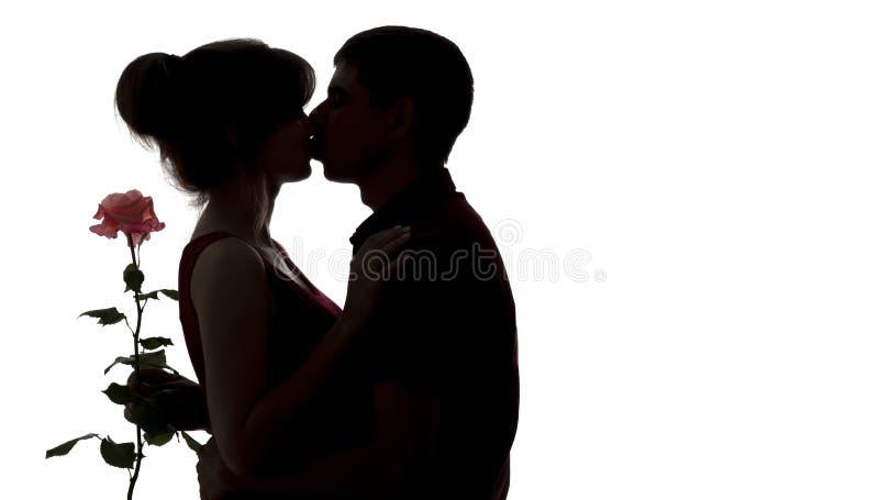 Het silhouet van een jong paar in liefde op wit isoleerde achtergrond, man namen de kussende vrouw en het houden bloem, concepten royalty-vrije stock foto