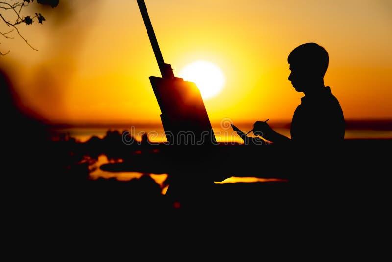 Het silhouet van een jonge mens die een beeld op linnen op een schildersezel schilderen in openlucht, het profiel van het schilde royalty-vrije stock foto