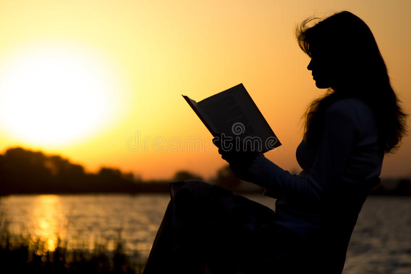 Het silhouet van een jonge mooie vrouw bij dageraadzitting op het vouwen zit en zorgvuldig het staren bij het open boek voor stock afbeelding