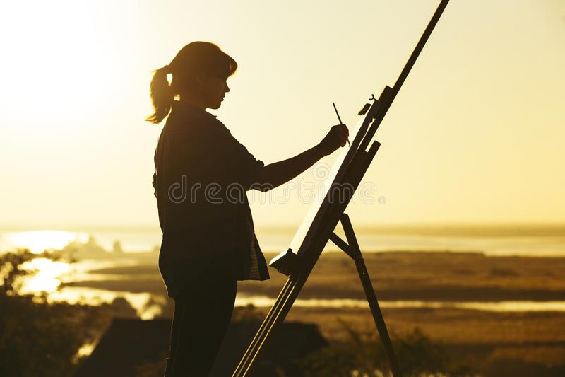 Het silhouet van een jonge vrouw die een beeld op een schildersezel op aard, meisjescijfer met borstel en het palet van de kunste royalty-vrije stock fotografie