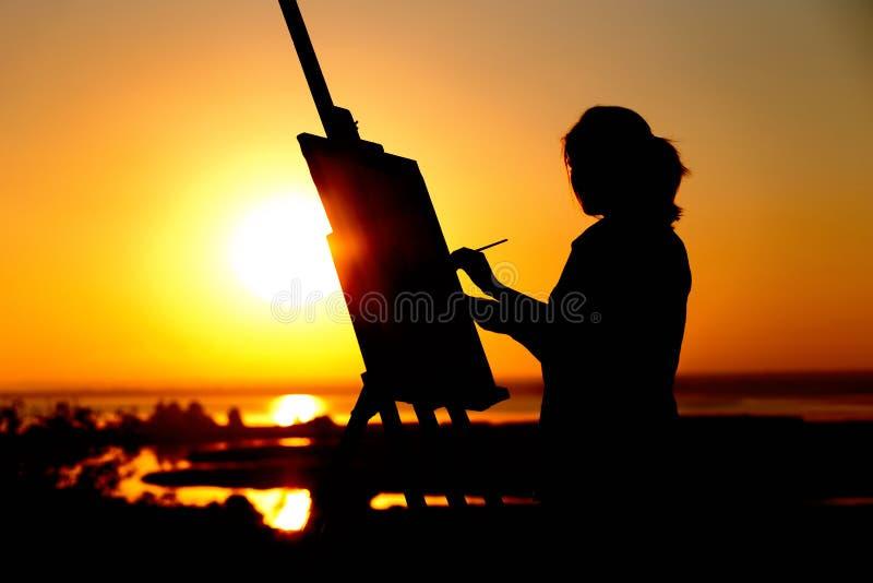 Het silhouet van een jonge vrouw die een beeld op een schildersezel op aard, meisjescijfer met borstel en het palet van de kunste stock afbeeldingen