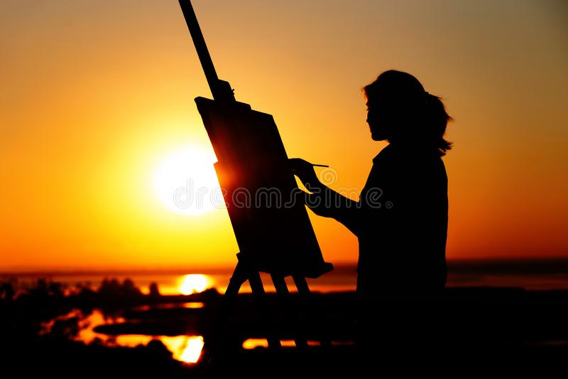 Het silhouet van een jonge vrouw die een beeld op een schildersezel op aard, meisjescijfer met borstel en het palet van de kunste royalty-vrije stock foto's