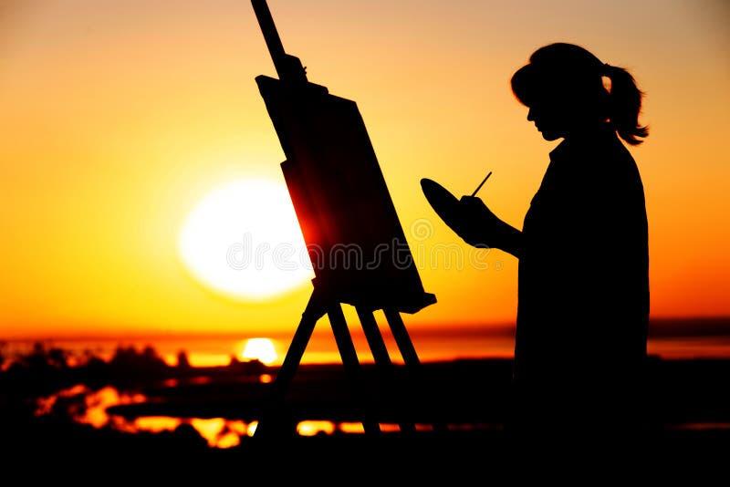 Het silhouet van een jonge vrouw die een beeld op een schildersezel op aard, meisjescijfer met borstel en het palet van de kunste stock afbeelding