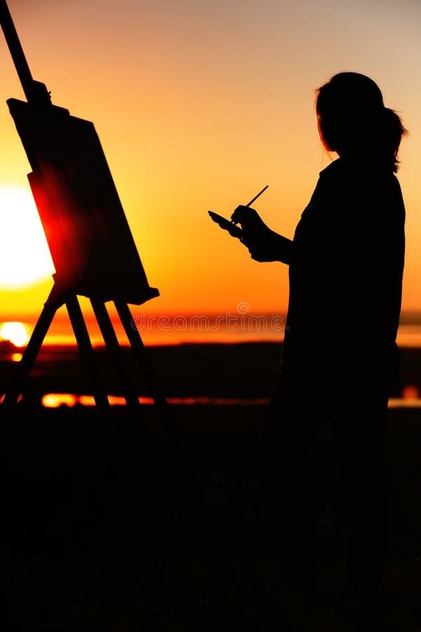 Het silhouet van een jonge vrouw die een beeld op een schildersezel op aard, meisjescijfer met borstel en het palet van de kunste stock foto