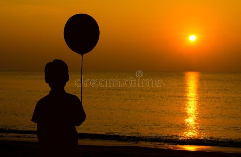 Het silhouet van een jongensholding ballon en het kijken zonsondergang op is stock afbeeldingen