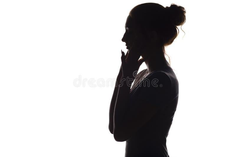 Het silhouet van een kalme jonge vrouw op een wit isoleerde achtergrond, cijfer van meisje met handen op haar gezicht stock foto's