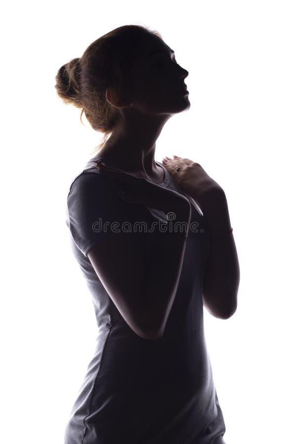 Het silhouet van een kalme jonge vrouw op een wit isoleerde achtergrond, cijfer van slank peinzend meisje royalty-vrije stock afbeeldingen