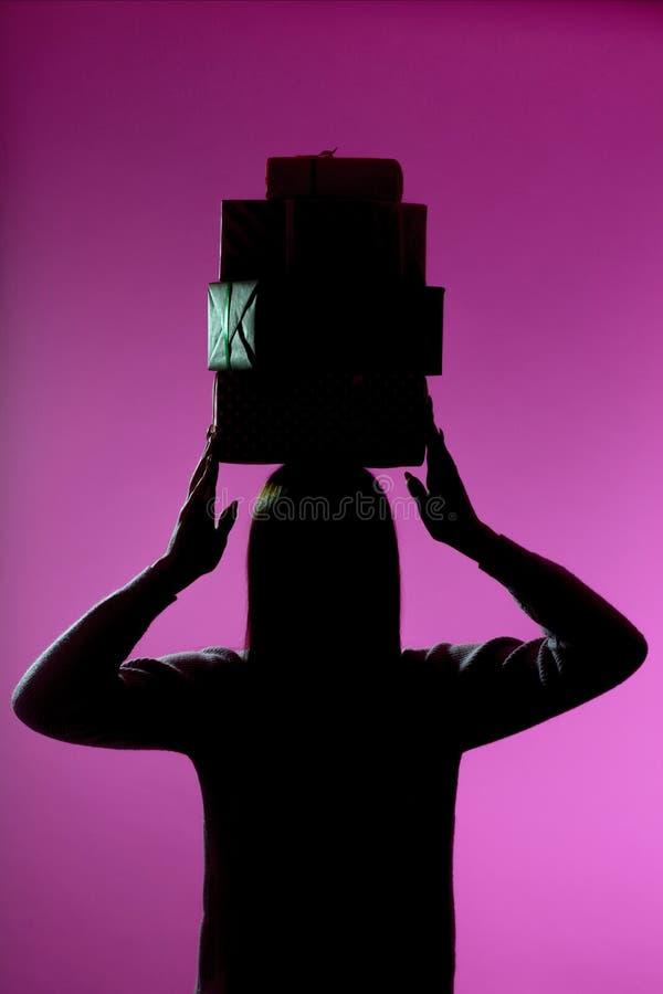Het silhouet van een meisje met een stapel giftdozen op haar hoofd, cijfer van een vrouwenholding stelt, concept vakantie voor stock foto