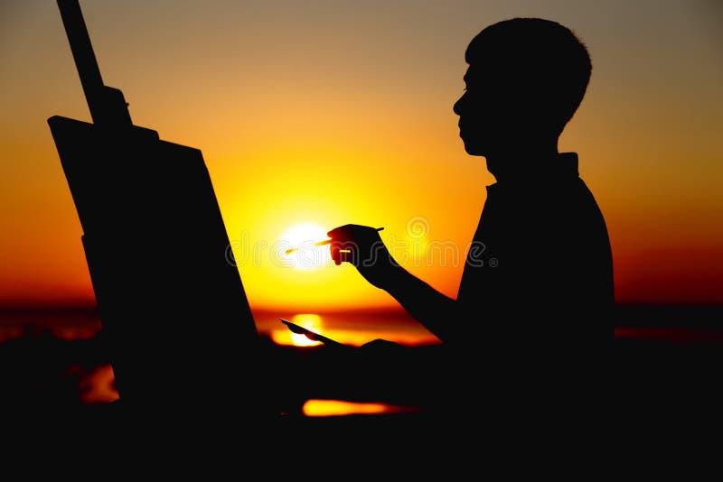 Het silhouet van een mens die een beeld op linnen op een schildersezel op aard, het profiel van het schildersgezicht schilderen n stock afbeeldingen