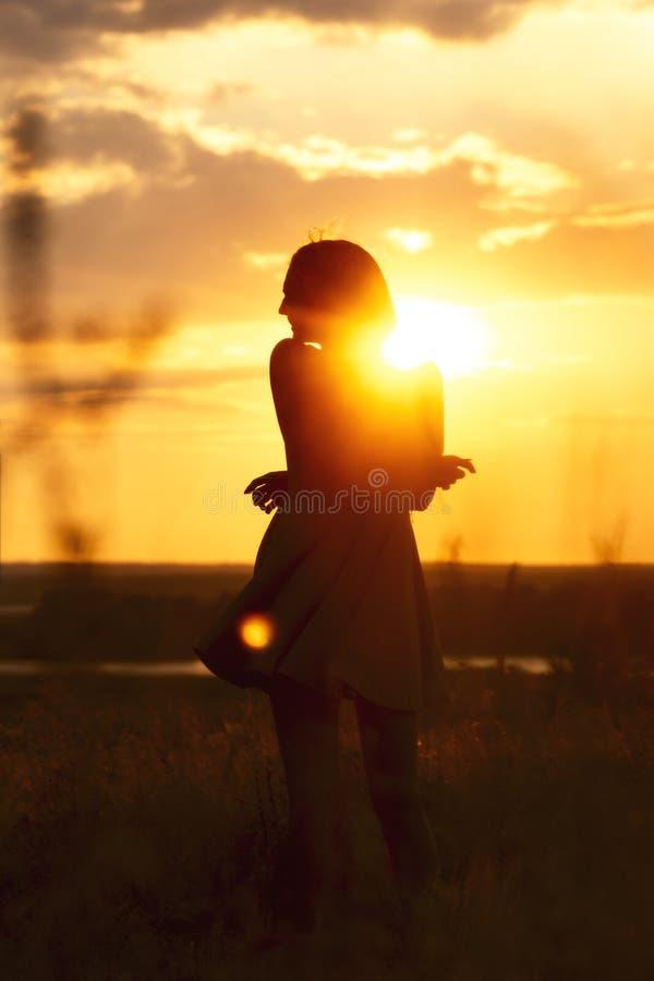 Het silhouet van een mooi dromerig meisje in een kleding bij zonsondergang op een gebied, een jonge vrouw met haar haar geniet va royalty-vrije stock foto's