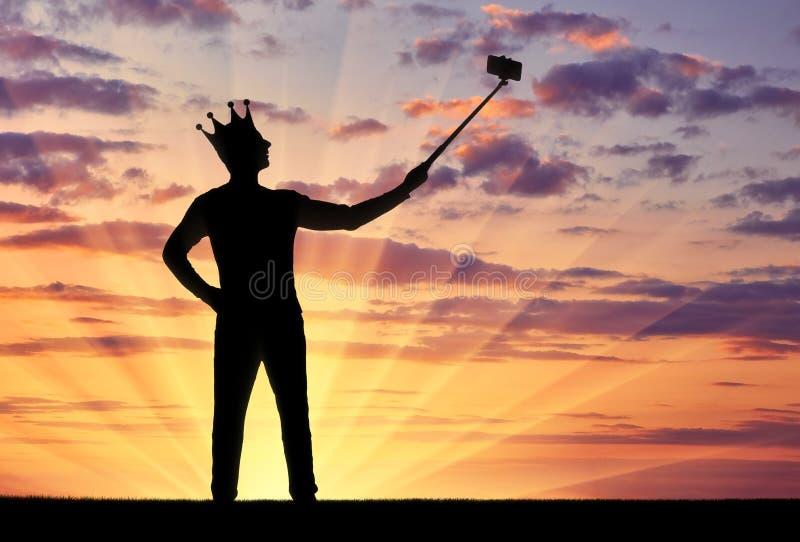 Het silhouet van een narcistische en egoïstische mens met een kroon op zijn hoofd, maakt selfie op de telefoon royalty-vrije stock fotografie