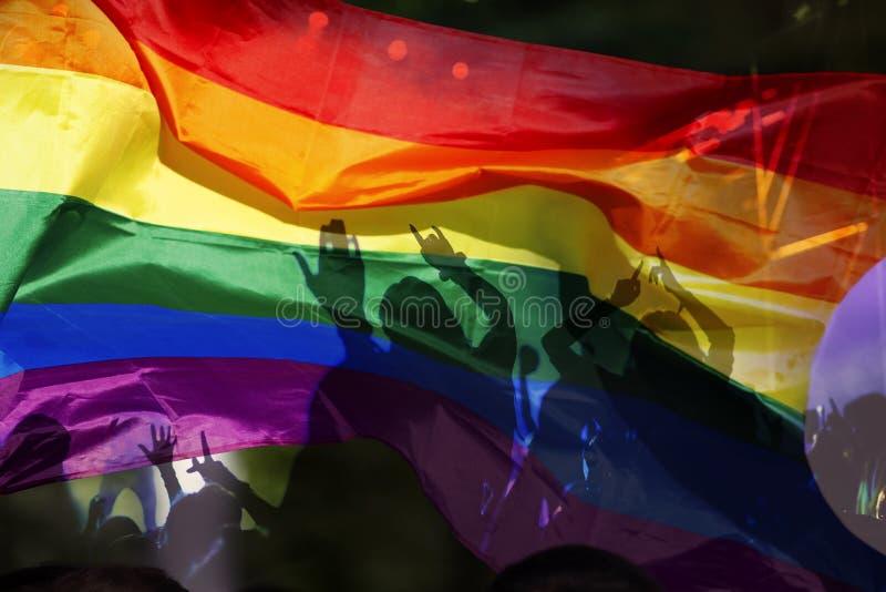 het silhouet van een parade van homosexuelen en de lesbiennes met een regenboog markeren - symbool van liefde en tolerantie royalty-vrije stock afbeeldingen