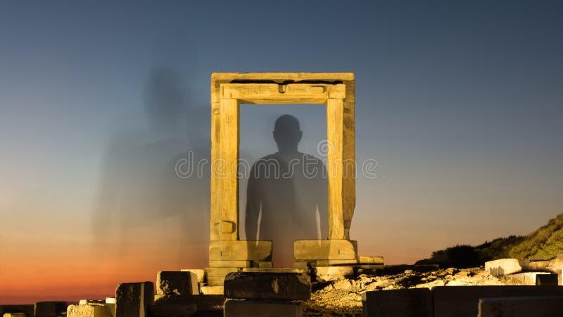Het silhouet van een persoon verdwijnt door een verlichte oude poort aan ruimte royalty-vrije stock afbeeldingen