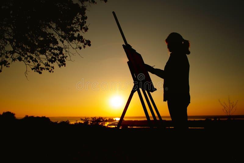 Het silhouet van een vrouw die een beeld met verven op canvas op een schildersezel, meisje met verfborstel en palet schilderen na stock foto's