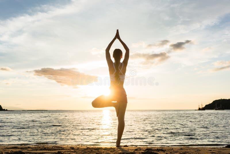 Het silhouet van een vrouw die de boomyoga uitoefenen stelt op een strand a stock foto's