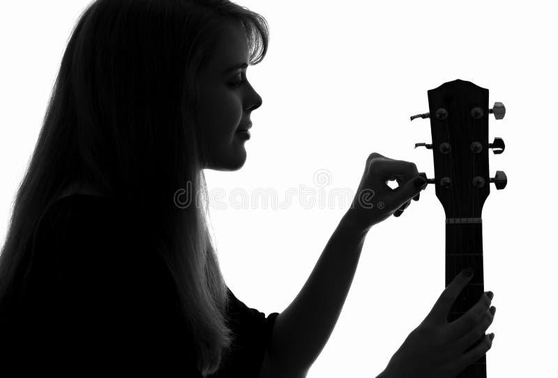 Het silhouet van een vrouw vormt een gitaar stock foto's