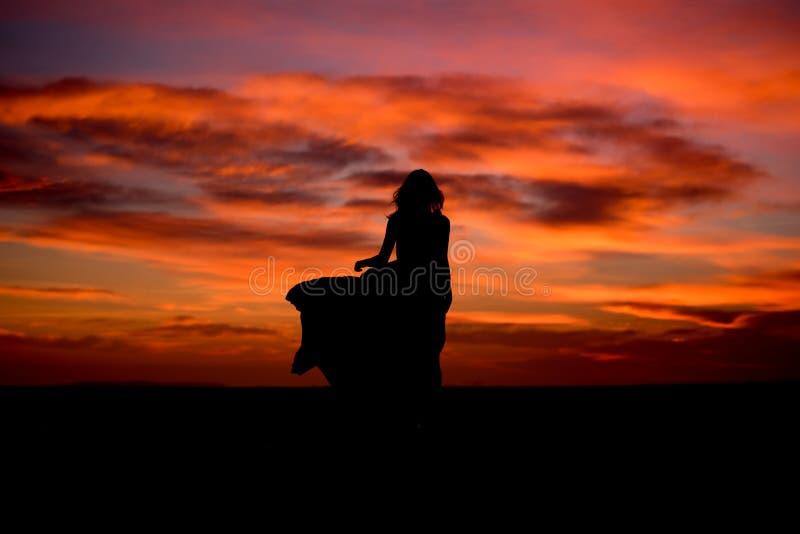 Het silhouet van een vrouw in zonsondergang met kleding en het haar blazen door de wind royalty-vrije stock foto