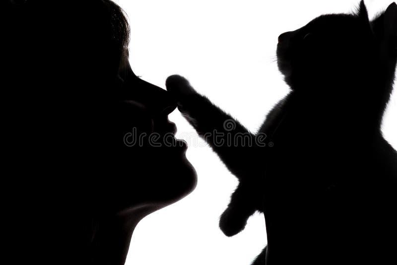 Het silhouet van een vrouwelijk gezicht met een klein katje dat een poot op de neus van meisje op wit zette isoleerde achtergrond royalty-vrije stock afbeeldingen