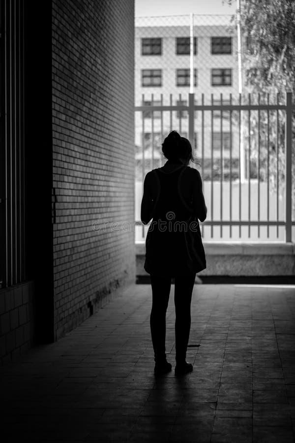 Het silhouet van een wijfje die zich in een smalle steeg dichtbij een bakstenen muur bevinden schoot in zwart-wit royalty-vrije stock afbeeldingen