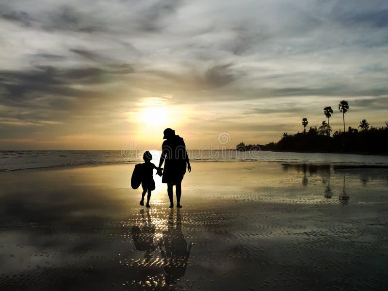 Het silhouet van familie die op de zonsopgang op het strand letten royalty-vrije stock fotografie