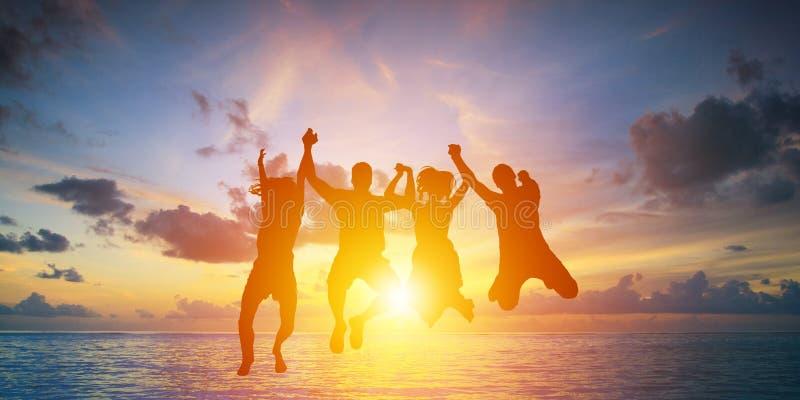 Het silhouet van gelukkig commercieel team die hoog dient de achtergrond van de zonsonderganghemel maken in stock afbeeldingen
