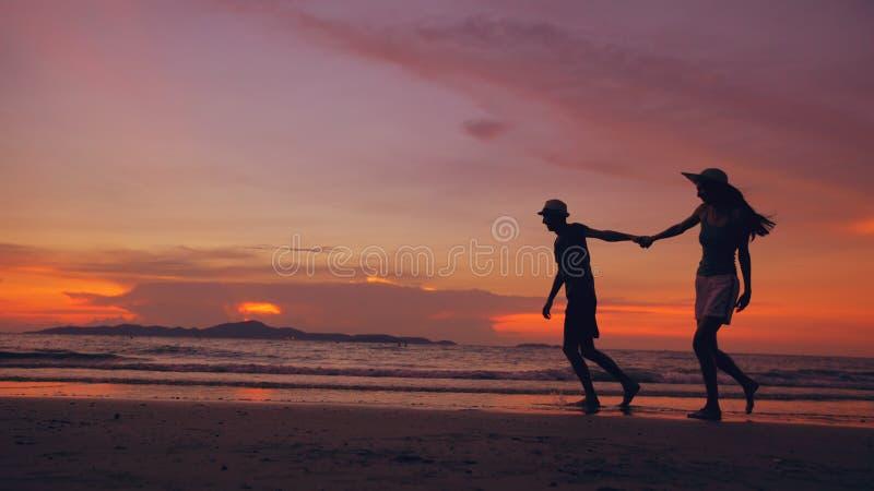 Het silhouet van gelukkig houdend van paar komt en speelt bij het strand op zonsondergang in oceaankust samen stock afbeelding