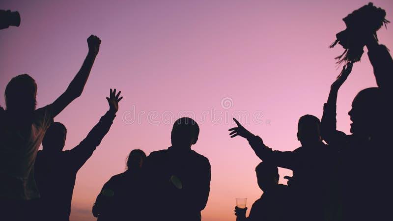 Het silhouet van Groeps jonge dansende mensen heeft een partij bij strand op zonsondergang royalty-vrije stock fotografie