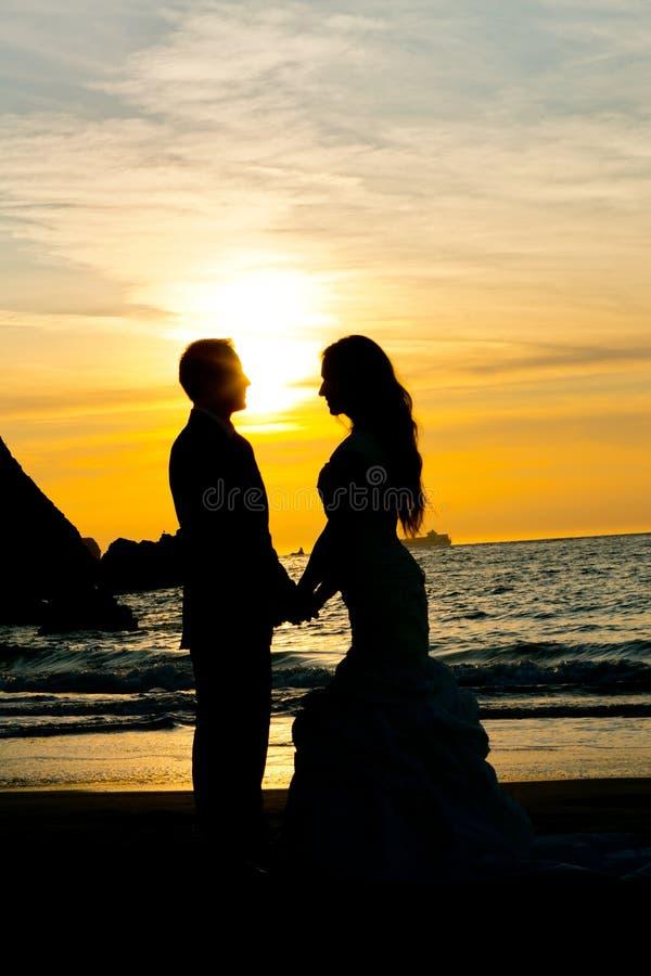 Het silhouet van het huwelijkspaar op de handen van de strandholding royalty-vrije stock afbeelding