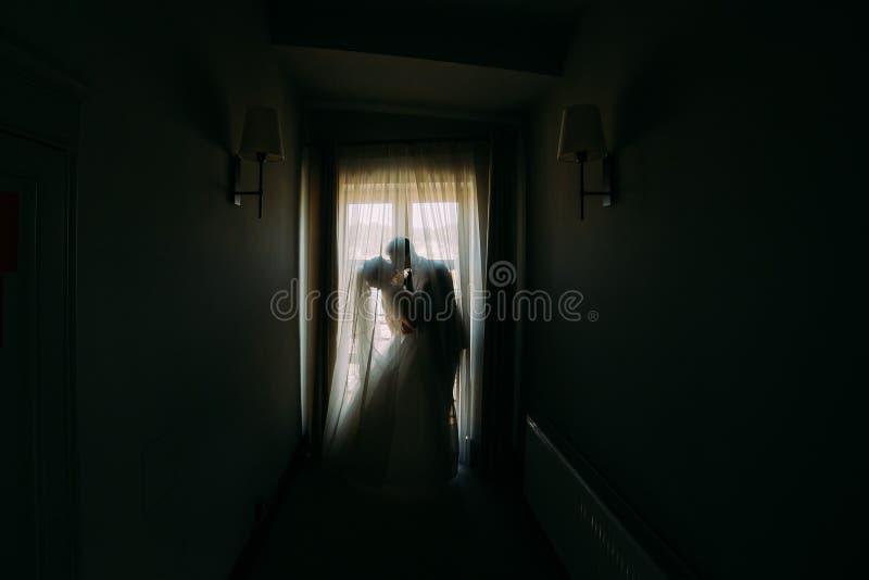 Het silhouet van het kussende jonggehuwdepaar die zich dichtbij het venster in de donkere ruimte bevinden stock afbeelding