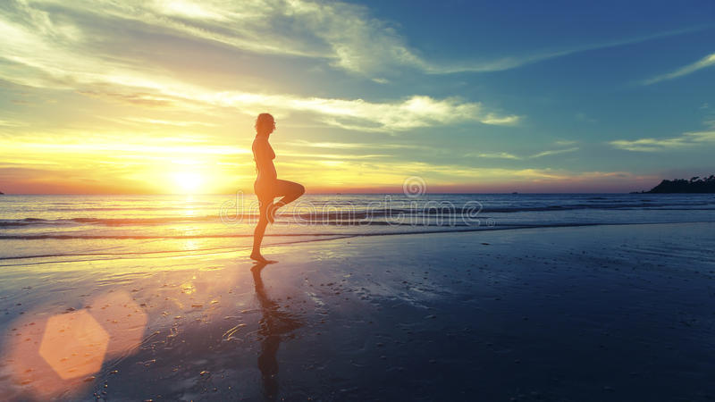 Het silhouet van jong meisje oefent op het overzeese strand uit tijdens een verbazende zonsondergang royalty-vrije stock fotografie