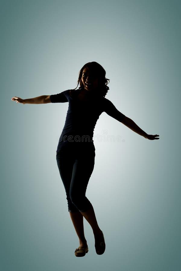 Het silhouet van jonge Aziatische vrouw stelt stock foto's