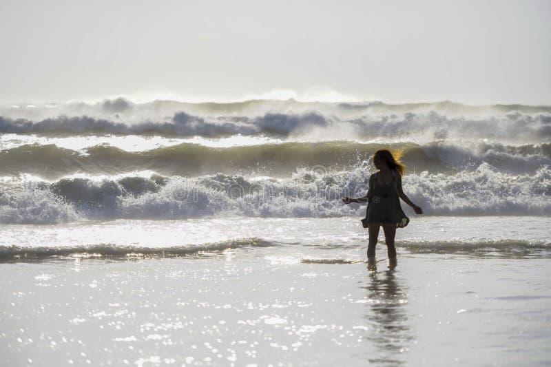 Het silhouet van jonge gelukkige Aziatische vrouw ontspande het bekijken wilde overzeese golven op zonsondergang tropisch strand royalty-vrije stock afbeelding